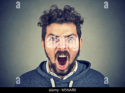 Young bearded man looking at camera and shouting expressively in fury.