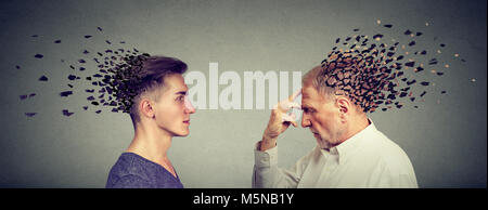 Memory loss due to dementia or brain damage. Side profile of young and senior men losing parts of head as symbol - Stock Photo