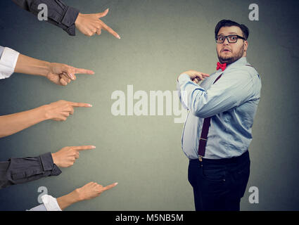 Blaming you. Anxious surprised business man judged by different people pointing fingers at him. Accusation of guilty - Stock Photo