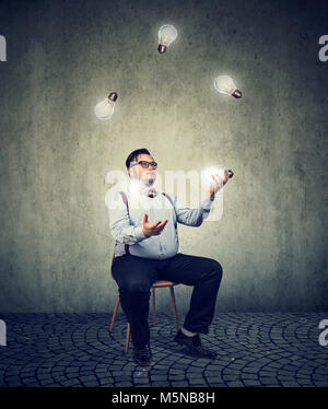 Young chubby man sitting on chair and juggling with light bulbs being genius. - Stock Photo
