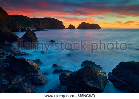 A fiery sunset colors the sky over Bird Island and the southern cliffs of the Marin Headlands, part of the Golden - Stock Photo