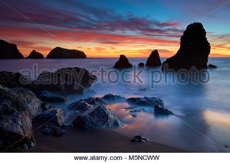 A fiery sunset stretches across Rodeo Cove, reaching from the sea stacks to Bird Island in the Marin Headlands near - Stock Photo