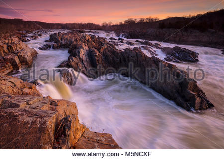 Under a red sunrise, the Potomac River drops 76 feet (23 meters) in a series of rapids at Great Falls Park, Virginia. - Stock Photo