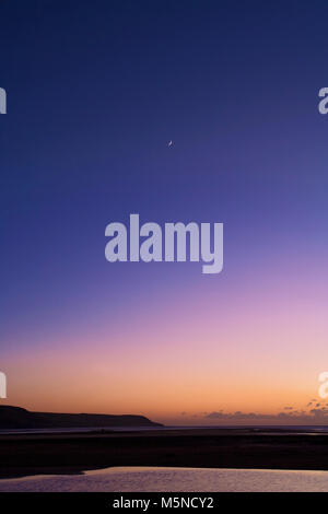 A new moon adds a focal point to a sunset over Barmouth Bay, Wales. - Stock Photo