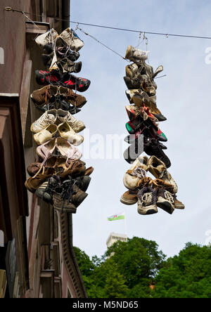 Group of shoes hanging from cables in the Ljubljana Streets with city flag - Stock Photo