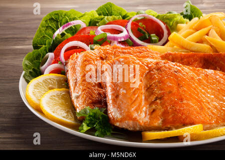Fried salmon with french fries  and vegetables on wooden table - Stock Photo