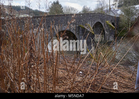 Looking from upstream at a wintery Westerkirk Bridge over the river Esk from the north bank. A category A listed - Stock Photo