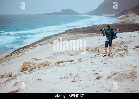 Photographer admitting unique others worldly landscape of sand dunes volcanic cliffs on the Atlantic coast. Baia - Stock Photo