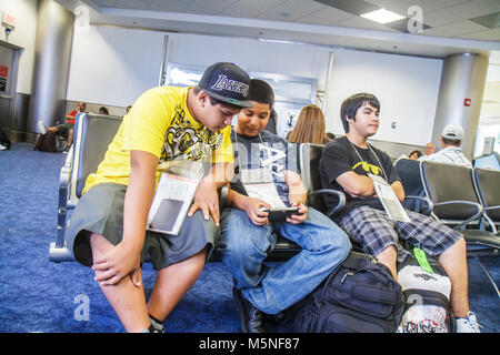 Miami Florida International Airport MIA gate area Hispanic teen adolescent boy passport around neck playing electronic - Stock Photo