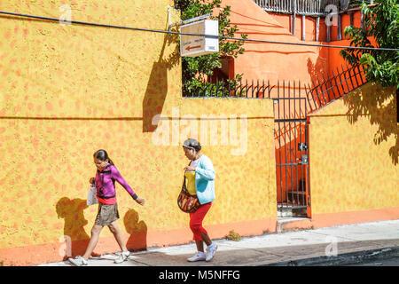 Cancun Mexico Yucatán Peninsula Quintana Roo Hispanic sidewalk yellow wall gate woman girl teen mother daughter - Stock Photo