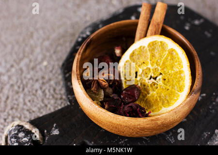 Dry ingredients spices for mulled wine in wooden bowl on grey concrete background - Stock Photo