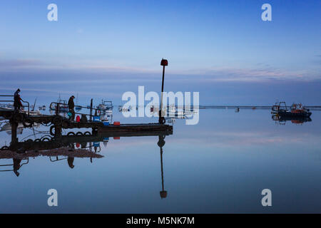 Two fisherman waiting for the boat to collect them from the jetty at Felixstowe Ferry in Suffolk, England. - Stock Photo