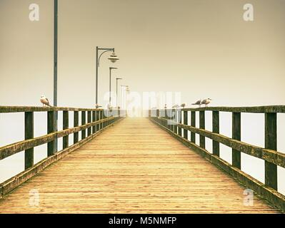 Empty wooden pier in harbor. Steel lamp post, horizon hidden in thick fog. Autumn mist on beach bridge  above sea - Stock Photo