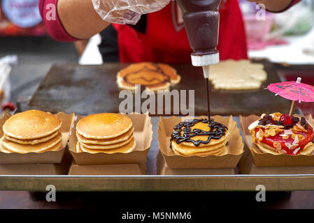 Thailand street food vendor preparing and decorating filled pancakes. Derived From American style  pancakes. 1 of - Stock Photo