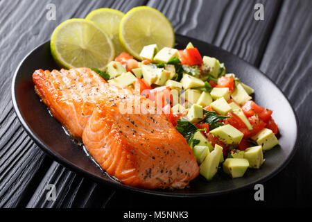 spicy baked salmon steak and fresh vegetable salad close-up on a plate. horizontal - Stock Photo