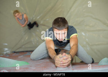 Downward view of man gripping climbing wall - Stock Photo