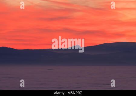 View from mountain Schoeckl over low stratus to Pack pass and mountain Triglav to sunset - Stock Photo