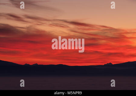 View from mountain Schoeckl in Styria over low stratus to mountain ranges Pack and Karawanks and Triglav to sunset - Stock Photo