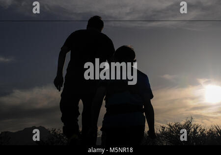 silhouettes of people walking in the Nevada desert as the sun goes down after a hot sunny day - Stock Photo