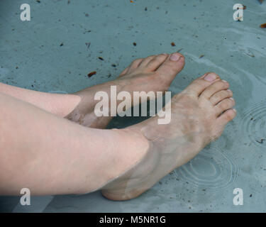 Woman's bare feet in the fountain water during hot summer day - Stock Photo