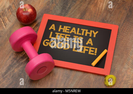 A Healthy Life is a good one chalkboard with dumbbell sign - Stock Photo