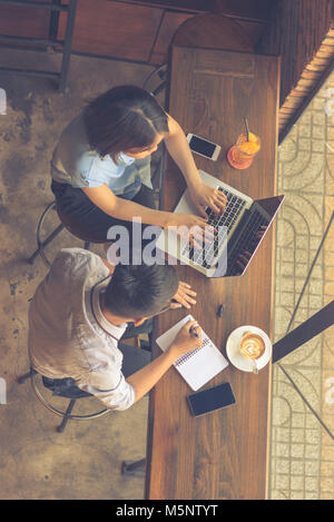 Top view of two employees working on laptop - Stock Photo