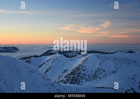 Colorful sunset at the summit of Ponten mountain in winter. View to Grünten mountain. Allgaeu Alps, Bavaria, Germany - Stock Photo
