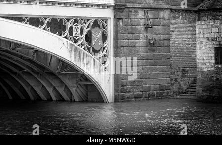 A black & white close-up view of Lendal Bridge in York.  Old stone steps lead down to a fast flowing river with - Stock Photo