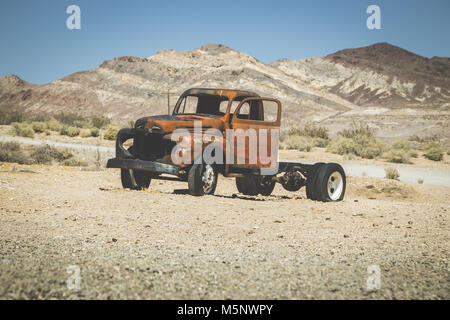 Classic view of an old rusty pickup truck car wreck in the desert on a beautiful sunny day with blue sky in summer - Stock Photo