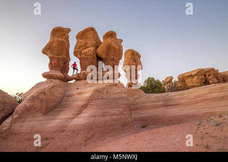 Hiker standing between hoodoos sandstone formations at sunset in Devil's Garden, Grand Staircase-Escalante National - Stock Photo