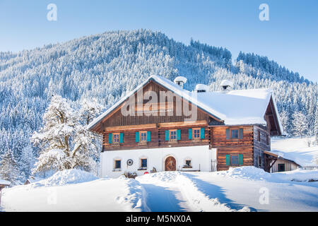 Panoramic view of old traditional farmhouse sitting on top of a hill in scenic winter wonderland scenery in the - Stock Photo