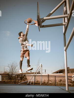 An outdoor shoot of a basketball player in Devizes, Wiltshire. Shot in natural sunlight on a basketball court. Wide depth of filed, good lighting.