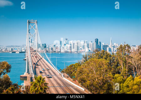 Classic panoramic view of San Francisco skyline with famous Oakland Bay Bridge illuminated on a beautiful sunny - Stock Photo