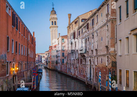Classic Venice city scene with beautiful canal and church tower in the background in beautiful evening twilight - Stock Photo