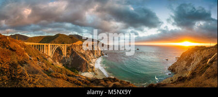Panoramic view of historic Bixby Creek Bridge along world famous Highway 1 in beautiful golden evening light at - Stock Photo
