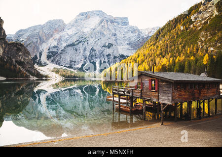 Scenic panoramic view of traditional wooden boathouse on the shores of famous Lago di Braies with Dolomited mountain - Stock Photo