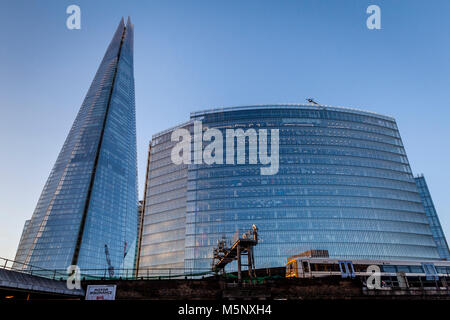 A Commuter Train Passes The Shard and The News Building, London Bridge Quarter, London, UK - Stock Photo