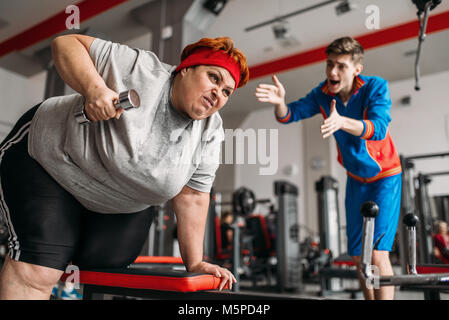 instructor forces fat woman to exercise hard workout in