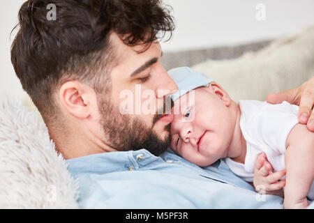 Loving happy father holds newborn baby in the arms - Stock Photo