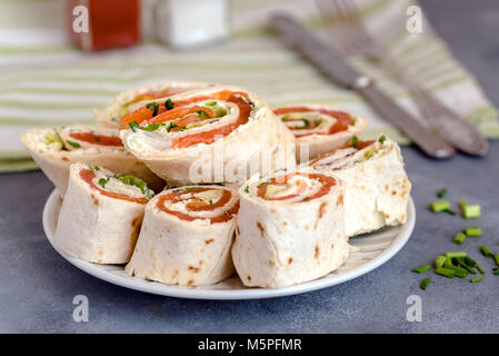 Rolls of thin pancakes with smoked salmon, cream cheese, chives and lettuce. - Stock Photo