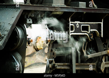 Steam escaping from release valves on the drive train of a refurbished vintage steam locomotive - Stock Photo