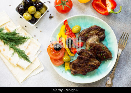 Appetizing barbecue steak from beef sirloin full roast served with fresh vegetable salad.