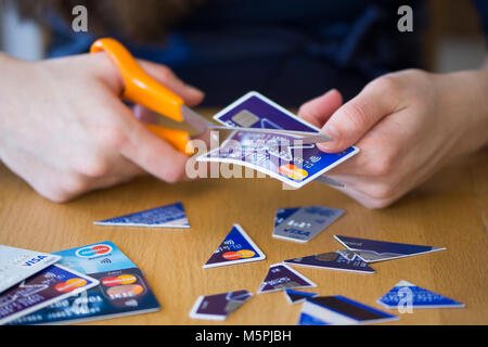 A woman cutting up credit cards - credit card debt concept - Stock Photo