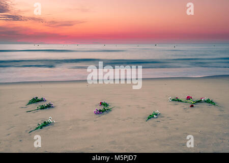 Flowers from religious procession on august 15 left at the beach at the end of the day - Stock Photo