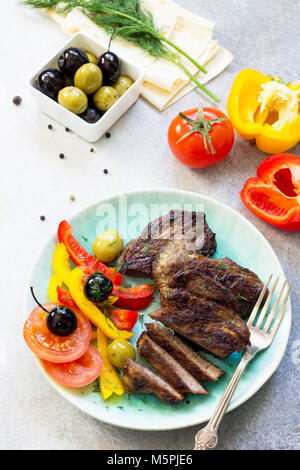 Appetizing barbecue steak from beef sirloin full roast served with fresh vegetable salad. - Stock Photo