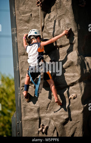 A boy in safety harness climbing up a artificial rock outdoor - Stock Photo