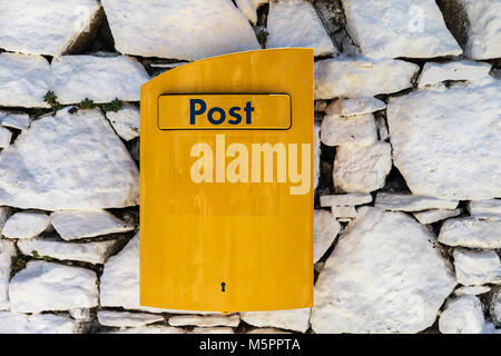 Yellow post box on grey stone fence. - Stock Photo