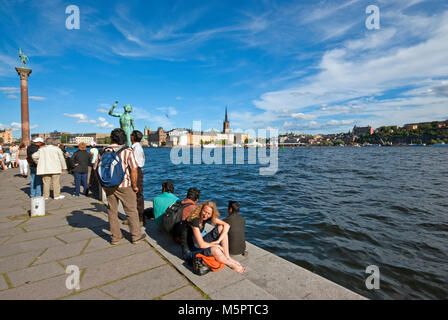 People relaxing in the City Hall park near statue by Carl Eldh (The Song) and pillar with statue of Engelbrekt Engelbrektsson, - Stock Photo