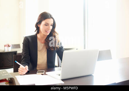 Shot of a beautiful young businesswoman using laptop and doing some paperwork while working on laptop. - Stock Photo