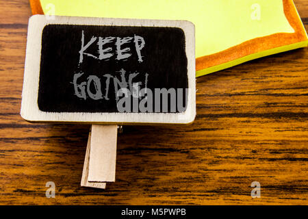 Handwritten text showing Keep Going. Business concept for Go Moving Forward Letting written on announcement board - Stock Photo